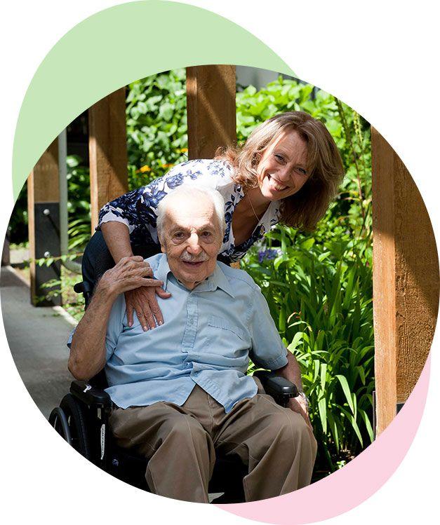 Female helping elderly man in wheelchair